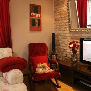 Klasyczny styl salonu podkreśla obity bordowym welurem fotel bujany. Tuż nad nim obraz autorstwa artystki Marty Mężyńskiej. Fot. Bartosz Jarosz.