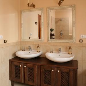 Stylizowane, dębowe szafki w ciemnym kolorze zaprojektowane zostały specjalnie pod umywalki. Tuż nad nimi lustra w stylowej, bogato zdobionej oprawie, których czar uzupełniają XIX-wieczne, złocone kinkiety. Fot. Bartosz Jarosz.