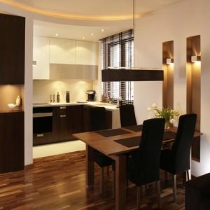 Kuchnia komponuje się z jadalnią i salonem za sprawą zastosowania tej samej kolorystyki. Podwieszany sufit w formie łuku sprawia, że strefa kuchenna ma otwarty charakter. Oświetlenie halogenowe i liniowe potęguje ten efekt. Fot. Bartosz Jarosz.