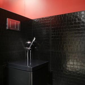 Nieco mroczne, czarne płytki fakturze skóry krokodyla ułożono na podłodze oraz fragmencie ścian. Kwadratowy sedes jest równie czarny, jak tło. Fot. Bartosz Jarosz.