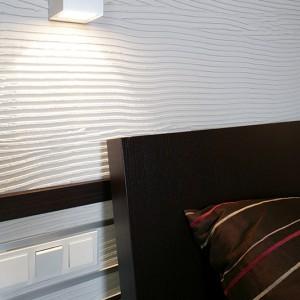 Nieco dynamiki do wnętrza wprowadza charakterystyczna struktura ściany za łóżkiem. Na cofniętej lekko płaszczyźnie, w warstwie specjalnego kleju, wykonano grzebieniem nieregularne wzory. Fot. Monika Filipiuk.