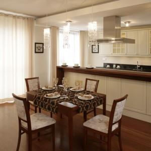Stół jadalniany i zestaw krzeseł (Swarzędz) ustawiono na pograniczu stref salonu i kuchni. Strefa jadalniana posiada własne oświetlenie w postaci trzech wiszących lamp. Fot. Bartosz Jarosz.