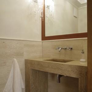 Ława z umywalką, w toalecie gościnnej, została wykonana z beżowego trawertynu żywicowanego. W sąsiedztwie kryształowa lampa i lustro w ramie fornirowanej drewnem jatoba. Fot. Bartosz Jarosz.