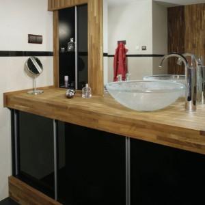Zastosowanie egzotycznego drewna tekowego w łazience okazało się bardzo trafnym pomysłem, gdyż ociepliło surową czerń oraz sterylną biel. Na tym zaś właśnie zależało właścicielom, którzy chcieli, by nowoczesny wystrój nie był zbyt chłodny i techniczny. Fot. Monika Filipiuk.