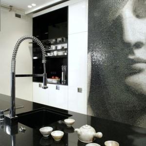 Z czarnego szkła wykonane zostały półki, m.in. na akcesoria do kawy. Wokół widać liczne szafki i zabudowaną lodówkę. Fot. Monika Filipiuk.