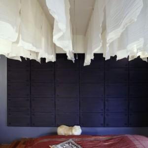Ściany zostały pokryte panelami, tapicerowanymi jedwabiem w ciemnogranatowym kolorze. Intrygujące rzeczy dzieją się pod sufitem: zawieszono tam rzędy białych tkanin, pomiędzy którymi zainstalowano światłowody. Łóżko przykryto oryginalną narzutą, uszytą z jedwabnego indyjskiego sari... Fot. Monika Filipiuk.