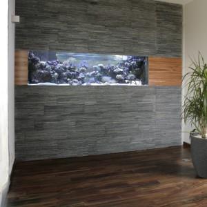 Akwarystyka to jedna z pasji pana domu. Z myślą o dużym akwarium morskim architektki  zaprojektowały specjalną ścianę pokrytą naturalnym łupkiem i dekoracyjnymi elementami z jabłoni indyjskiej. Fot. Bartosz Jarosz.