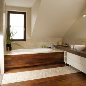 Wanna i umywalki mają opływowe kształty (Villeroy and Boch), doskonale wpisują się w kojąca, łagodną aranżację łazienki. Olejowane drewno teakowe na podłodze i obudowie wanny zestawiono z jasnymi płytkami gresowymi na ścianach. Fot. Bartosz Jarosz.