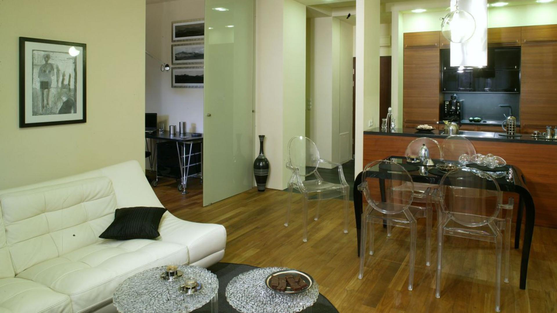 Po rozsunięciu drzwi z matowego szkła przestrzeń kuchni i salonu poszerza się o sypialnię. W obu wnętrzach widać podłogę z drewna tekowego. Fot. Monika Filipiuk.