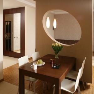 Choć szeroki otwór wejściowy zdaje się prowadzić z holu wprost na stół jadalniany, stojąca obok ścianka zapewnia jedzącej obiad rodzinie poczucie intymności i spokoju. Fot. Bartosz Jarosz.