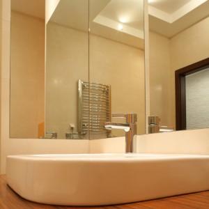 Zainstalowane pod kątem prostym tafle lustra wzbogacają układ przestrzenny łazienki i ułatwiają wykonanie perfekcyjnej fryzury pani domu. Fot. Bartosz Jarosz.