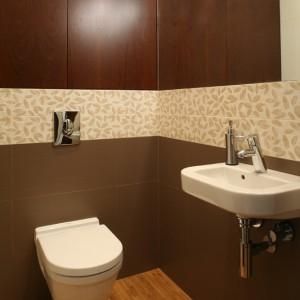 Wśród kilku odcieni brązu, które zdobią łazienkę, wyróżnia się brązowo-kawowy kolor drewna egzotycznego sucupira. Z fornirowanej płyty w tym kolorze wykonane zostały fronty łazienkowej szafki. Fot. Bartosz Jarosz.