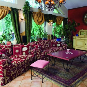 W salonie królują dwie wielkie kanapy i malinowy stolik, ale urządzanie tego wnętrza (jak i całego domu) zaczęło się tak naprawdę od kupna przedwojennej, pękatej komody. Po renowacji i zmianie koloru na żółty, mebel stanął w salonie. Fot. Bartosz Jarosz.