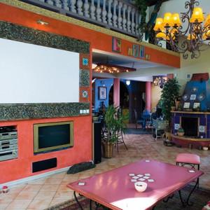 Wcześniej aranżacja salonu miała inne kolory, ale Kamilla Osiekowicz i Artur Szwedowski uznali, że czerwony kolor ścian jest lepszym rozwiązaniem, bo ciekawie ożywi całość. Podobnie jak efektowny ekran, na którym gospodarze wyświetlają ulubione filmy. Fot. Bartosz Jarosz.