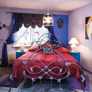 """Prawdziwą ozdobą sypialni jest wykute ze stali, według projektu Małgosi, łóżko. Nie bez powodu ma nietypową wysokość. Zarówno poprzedni, jak i obecni gospodarze, nie lubią wstawać rano """"na ugiętych nogach"""". Fot. Bartosz Jarosz."""