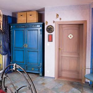 Ściany sypialni mają subtelny, wrzosowy odcień, któremu od czasu do czasu towarzyszy szeroki pas błękitu. Niebieski kolor ma także szafa, mebel, który jako pierwszy pojawił się w tym wnętrzu i jako jeden z pierwszych w domu. Fot. Bartosz Jarosz.