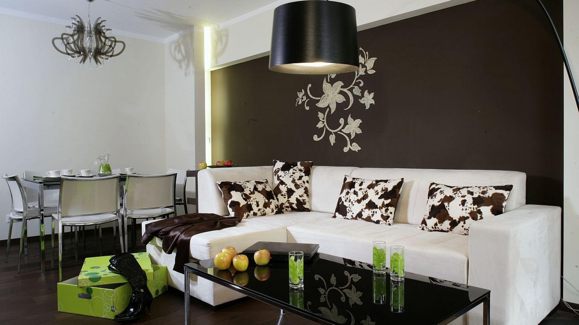 """Strefę jadalni akcentuje efektowny żyrandol – jego lekka forma nawiązuje do florystycznej dekoracji na ścianie salonu. Przy stole ustawione są krzesła """"Keyo"""" z oferty marki Bontempi Casa. Fot. Monika Filipiuk."""