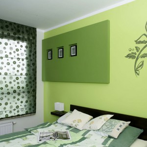 """W sypialni pojawia się nieco jaskrawsza """"plama"""" koloru. Jedną ze ścian pokrywa zieleń w dwóch różnych odcieniach, ozdobiona wykonanym za pomocą szablonu, roślinnym ornamentem. Fot. Monika Filipiuk."""