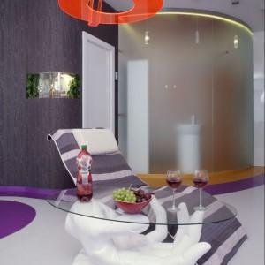 Łazienkę i sypialnię oddzielono od salonu niezwykle oryginalnie: za pomocą ścian w formie fali. I to jakich ścian! Łazienkę wydziela cienka ścianka ze szkła lakierowanego, a sypialnię ściana oklejona ozdobną tapetą w kolorze oberżyny z otworem na terrarium. Fot. Monika Filipiuk.