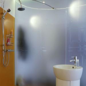 Łazienka zaskakuje pomysłowością na każdym kroku. Na ścianach, zamiast płytek, pomarańczowe szkło lakierowane i biała pleksi. Zrezygnowano z brodzika i kabiny prysznicowej, dzięki czemu łatwo utrzymać czystość. Szafka pod umywalkę jest wykonana z płyty mdf, giętej na rurze! Fot. Monika Filipiuk.