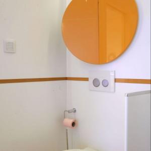 Pomarańczowe koła z połyskującego mdf-u nad sedesem, to coś więcej niż tylko dekoracje. Są to bowiem fronty szafek na kosmetyki. Listwa, także w kolorze pomarańczowym, wykonana jest ze szkła. Fot. Monika Filipiuk.