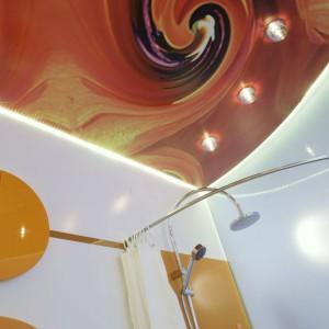 Sufit napinany (Olimp) wprowadza do łazienki sporą dawkę dynamiki, a to za sprawą szalonego nadruku, który stworzyła architekt. Oświetlenie górne tworzy rząd halogenów w szklanych oprawach. Fot. Monika Filipiuk.