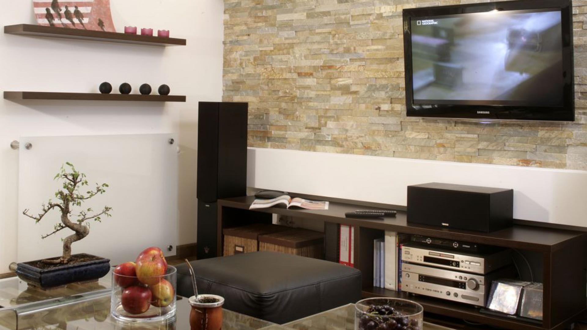 Jedna ze ścian w salonie została potraktowana szczególnie surowo. Wyłożona naturalnym łupkiem kamiennym stanowi oryginalne tło dla telewizora. Wokół rama z płyty kartonowo-gipsowej. Fot. Monika Filipiuk.