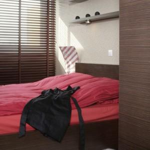 W sypialni odnajdziemy wiele estetycznych odniesień do salonu, których najlepszym odzwierciedleniem są użyte materiały oraz ich kolorystyka. Zdecydowanie królują tu drewno i czerwień. Fot. Monika Filipiuk.