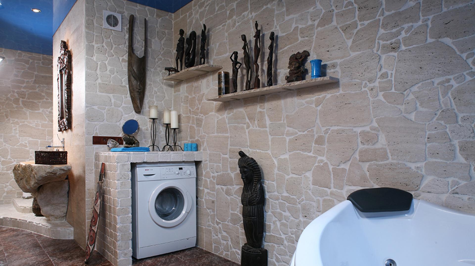 Aby pralka nie zakłócała swym prozaicznym widokiem artystycznej całości, obudowano ją trawertynowymi ściankami. Dodatkowy efekt – półka na świece. Fot. Bartosz Jarosz.