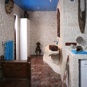 Obok drewnianego, egzotycznego siedziska, prosta szafka z białego MDF. Nie narzuca się ze swoją obecnością, a można w niej schować np. ręczniki. Fot. Bartosz Jarosz.