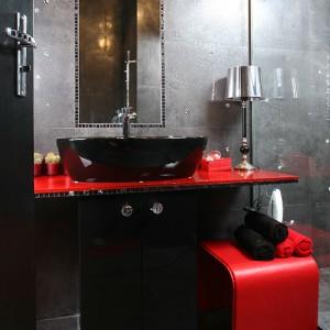 Grafitowa okładzina gresowa, imitująca polerowaną powierzchnię łupku, stanowi tło dla lśniącej czernią umywalki oraz szafki umywalkowej z czarnego MDF-u w połysku, zwieńczonej szklanym, czerwonym blatem. Fot. Bartosz Jarosz.