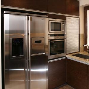 """Mikrofalówka, piekarnik (Siemens) i duża, """"amerykańska"""" lodówka (Samsung) zostały skupione z lewej strony kuchni. Za roletą schowano drobny sprzęt AGD – malakser, toster itp. Fot. Bartosz Jarosz."""