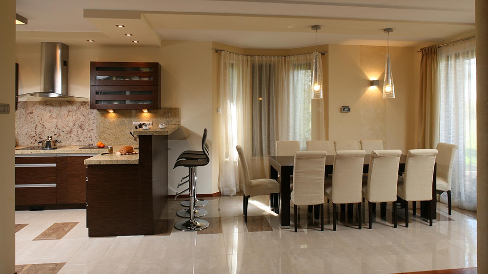 """Otwarta kuchnia tworzy wraz z jadalnią całość jednolitą pod względem kolorystyki, stylu i form. Wspólnie stanowią """"serce"""" gościnnego domu. Fot. Bartosz Jarosz."""