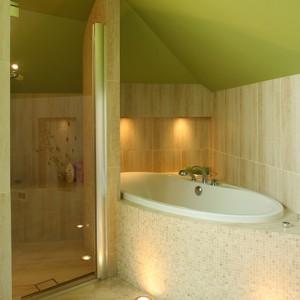 Wiele ścian zostało wyprofilowanych. W ten sposób w kabinie prysznicowej powstało wygodne siedzisko, a u wezgłowia wanny – miejsce na zainstalowanie halogenów. Fot. Bartosz Jarosz.
