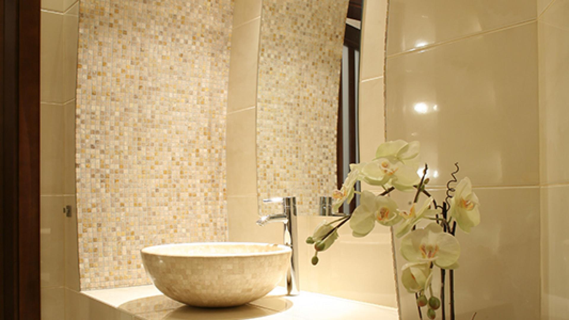 Umywalka i mozaika pochodzą z katalogu hiszpańskiej firmy Dune. Wykonane są z trawertynu. Fantazyjny blat umywalkowy ma wymodelowane miejsce na kwiaty. Fot. Bartosz Jarosz.