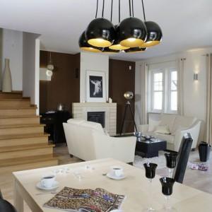 Oryginalna lampa rodem z pracowni fotograficznej i ustawione nad kominkiem zdjęcie sugerują, że potencjalnym mieszkańcem tego domu mógłby być artysta fotografik. Fot. Monika Filipiuk.