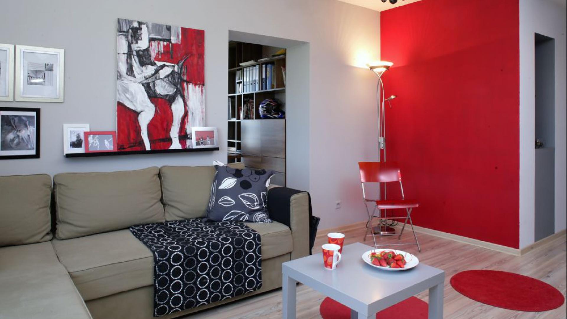 Za oliwkową kanapą (IKEA) utworzono swoistą domową galerię. Specjalne listwy pozwoliły niebanalnie wyeksponować obraz Anny Superniok oraz grafiki młodych artystów wyszukane przez architekt na digart.pl. Fot. Monika Filipiuk.