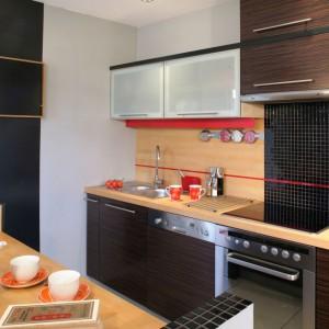 Meble kuchenne mają nowoczesną formę, którą ubarwiają fronty szafek fornirowane hebanem oraz szafek górnych ze szkła satynowego. Kontrastowo dobrano jasne blaty z litego drewna jesionowego. Fot. Monika Filipiuk.