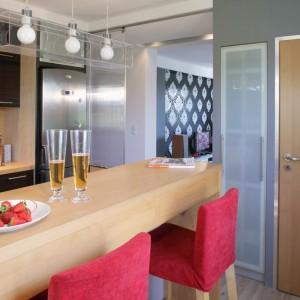 Przy kuchennym barze z drewna jesionowego ustawiono parę krzeseł barowych. Krzesła pochodzą z IKEA, ale ich indywidualne czerwone obicie nadała im architekt, dzięki czemu stały się bardziej wyraziste i odważne. Strefa ta ma własne oświetlenie w postaci designerskiej lampy z transparentnego pleksi (Trends). Fot. Monika Filipiuk.
