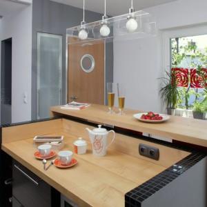Uroda nowoczesnej kuchni tkwi w detalach. Wyspę kuchenną podkreśla wykończenie z czarnej mozaiki (Tubądzin). Nie mniej efektownym smaczkiem jest niebanalna dekoracja okna z zawieszonych czerwonych paneli (Koziel). Fot. Monika Filipiuk.