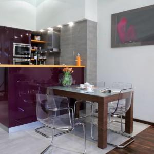 """Stół kuchenny, jak większość mebli, wykonany jest z drewna palisandrowego. Mebel, mimo monumentalnych nóg, nabiera lekkości za sprawą szklanego blatu i transparentnego otoczenia: krzeseł-""""duchów"""" z pleksi (IKEA). Fot. Monika Filipiuk."""
