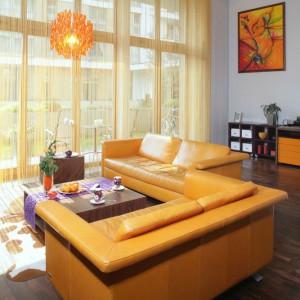Pomarańczowa barwa zdominowała strefę wypoczynkową, ale swoją energią emanuje znacznie dalej, bo jej moc odczuwalna jest w całym mieszkaniu. Sznurkowa firana (ADO Intarnational) okazała się idealnym rozwiązaniem przy olbrzymich oknach o niestandardowej wysokości. Fot. Monika Filipiuk.