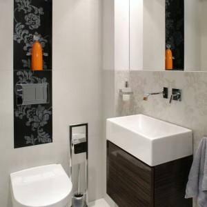 """Toaleta gościnna jest minimalistyczna. Tym bardziej kwiatowe dekory na ścianie nabierają w niej blasku. Wszystkie płytki pochodzą z oferty Resin. Hebanowa szafeczka eksponuje umywalkę """"Quadro"""" (Koło) i równie geometryczną baterię (Newform). Fot. Monika Filipiuk."""