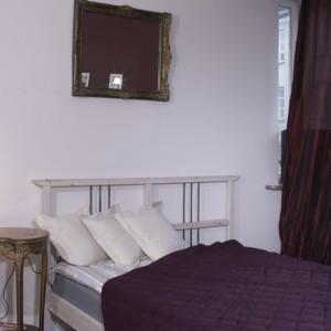 Pochodząca z przełomu XIX i XX wieku konsola to bardzo stylowy akcent w sypialni. Intarsjowany mebelek, oprócz funkcji dekoracyjnej pełni też rolę stolika nocnego. Fot. Monika Filipiuk.