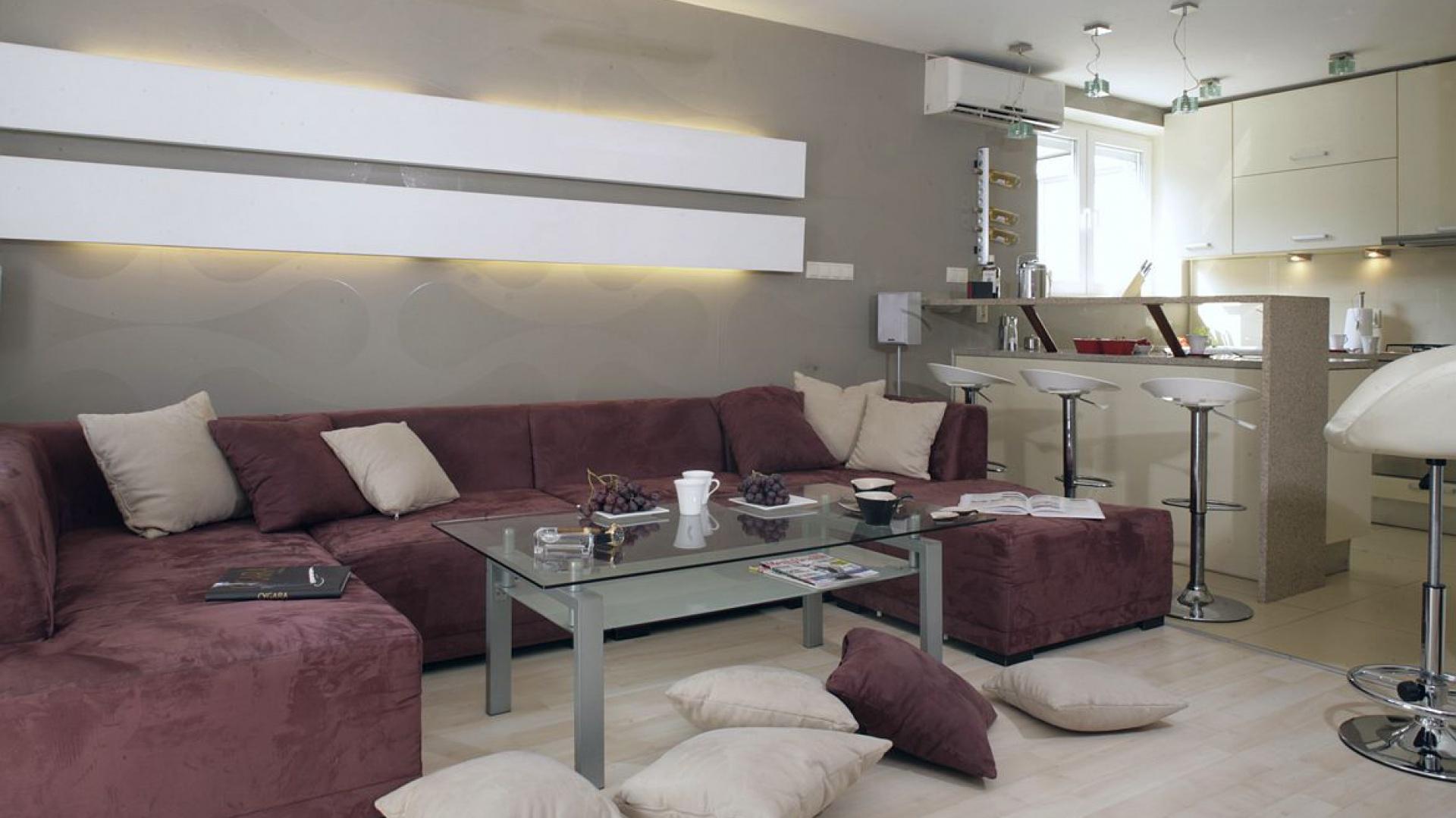 Nad narożną sofą w salonie zamontowano panel (płyta gipsowo-kartonowa) z ukrytą świetlówką.  Ścianę zdobi oryginalna tapeta nawiązującą wzorem do op-artu (Ulf Moritz). Pokryła ona ścianę w  salonie, kuchni i także w sypialni. Fot. Monika Filipiuk.