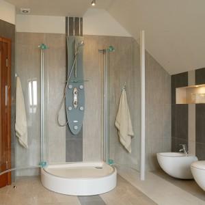 Mimo swych gabarytów, kabina prysznicowa nie odbiera łazience przestrzeni. Tafle szkła, których przejrzystości nie zakłócają ograniczone do minimum profile, są ledwie widoczne na szarym tle ścian. Fot. Monika Filipiuk.