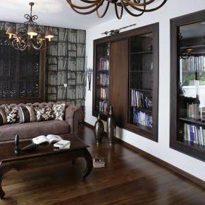 Klimat gabinetu buduje książkowa tapeta proj. P. Fornasettiego, marki Cole and Son. Prawdziwy księgozbiór został ustawiony we wnękach otoczonych drewnianą ramą jak z obrazu. W jednej z wnęk, za drewnianym panelem, ukryto również TV. Fot. Monika Filipiuk.