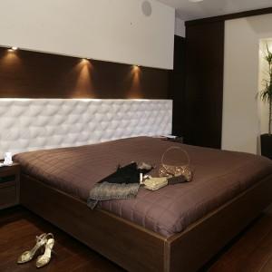 Pikowany kremową alkantarą zagłówek łóżka zajmuje znaczącą część ściany. Narzuca wnętrzu intymny, buduarowy charakter. Rama łóżka z drewna wenge, koresponduje z wypełnieniem znajdującej się nad nim wnęki (również fornir wenge). Fot. Monika Filipiuk.
