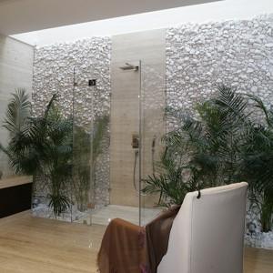 """W łazience panuje chłodny, kojący klimat. Narzuca go kamień trawertyn Classico, który pojawia się w dużej ilości: na podłodze, ścianie za wanną (""""Foster"""", Hoesch), a także w postaci pasa w kabinie prysznicowej. Fot. Monika Filipiuk."""