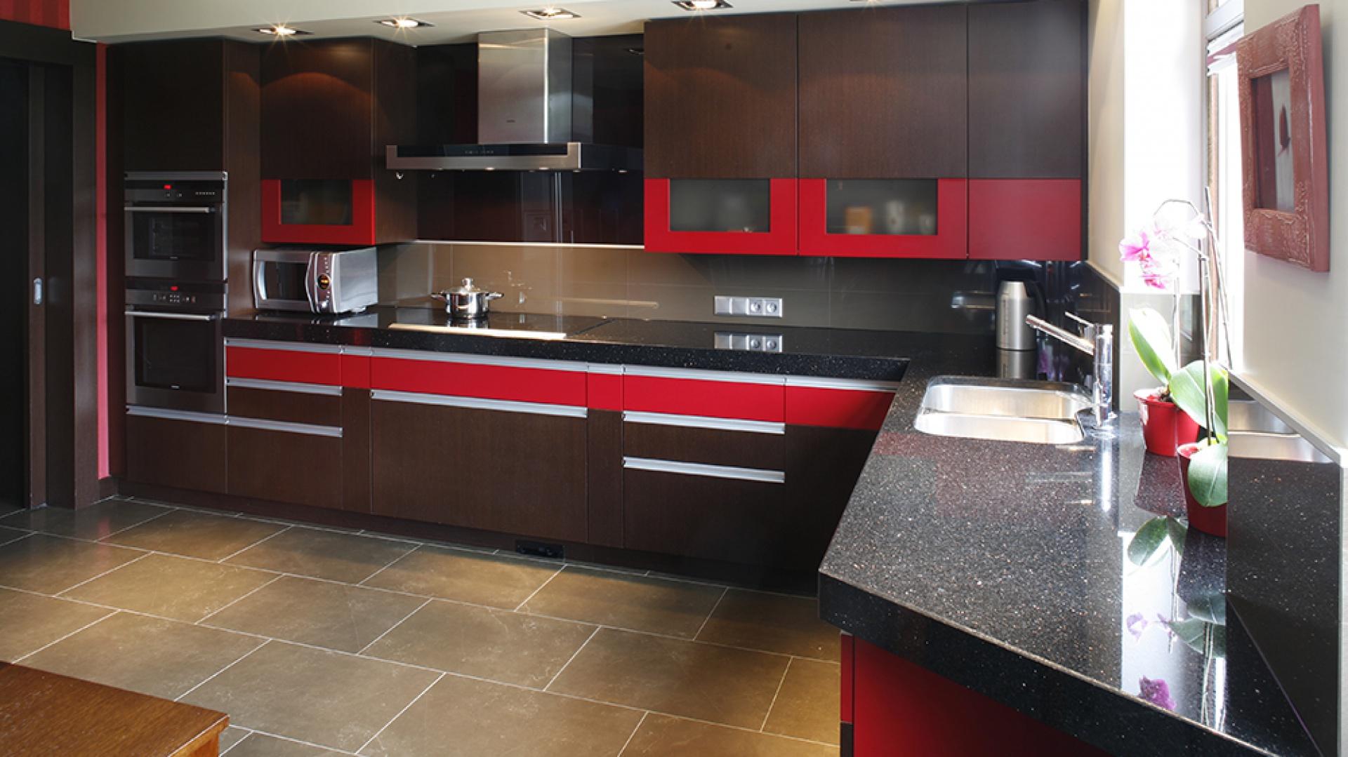 Ciekawe połączenie kolorów i oryginalne fronty meblowe odpowiadają za efektowny wygląd kuchni. Jej funkcjonalność gwarantuje duży blat roboczy z czarnego granitu oraz nowoczesne AGD: piekarniki, płyta grzejna i okap marki Siemens. Fot. Bartosz Jarosz.